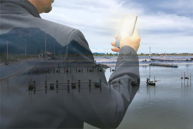 Uomo d'affari con lo smartphone sullo sfondo dell'allevamento di gamberetti