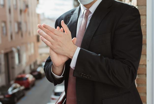 Uomo d'affari con giacca, cravatta e maschera che applaude le persone che stanno combattendo contro il coronavirus (covid19) dalla terrazza al tramonto