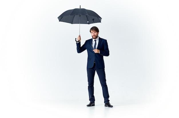 Uomo d'affari con un ombrello e in un abito classico in piena crescita su uno sfondo chiaro