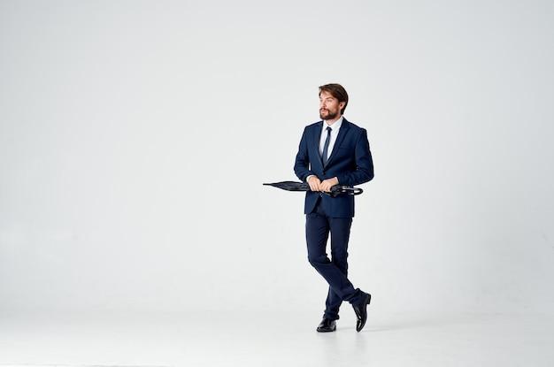 Uomo d'affari con un ombrello e in un abito classico in piena crescita in uno spazio luminoso