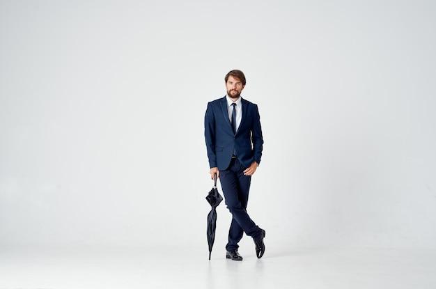 Uomo d'affari con un ombrello e in un abito classico in piena crescita su una luce.