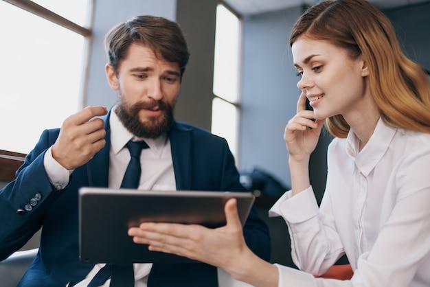 L'uomo e la donna d'affari comunicano con i professionisti dei gestori di tablet. foto di alta qualità