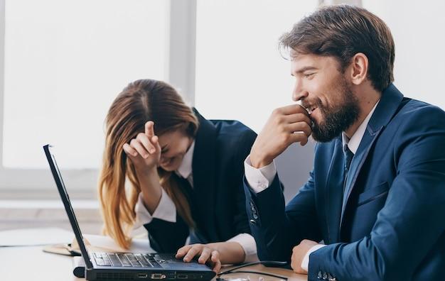 Uomo d'affari e donna di fronte a professionisti di colleghi di lavoro ufficio portatile. foto di alta qualità