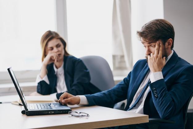 Uomo e donna d'affari in ufficio di fronte a un laptop funzionario del lavoro di carriera