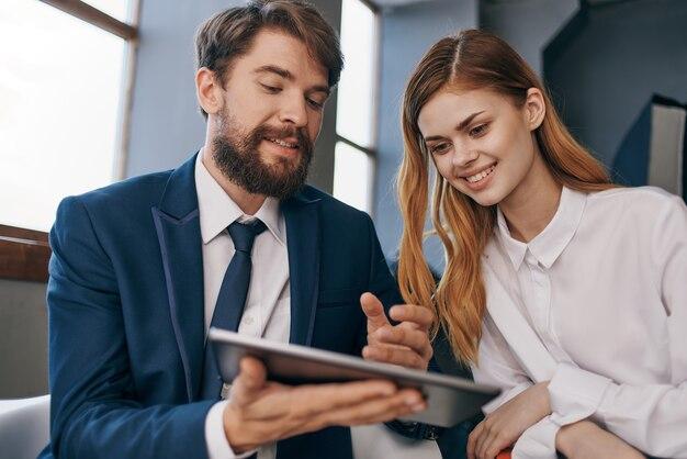 Un uomo e una donna d'affari lavorano con un ufficio tecnologico per tablet