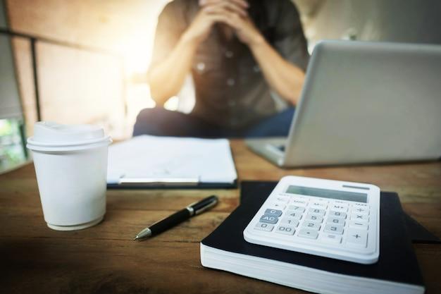 Uomo d'affari che lavora in un caffè con laptop, documenti finanziari e calcolatrice sul tavolo, messa a fuoco selettiva