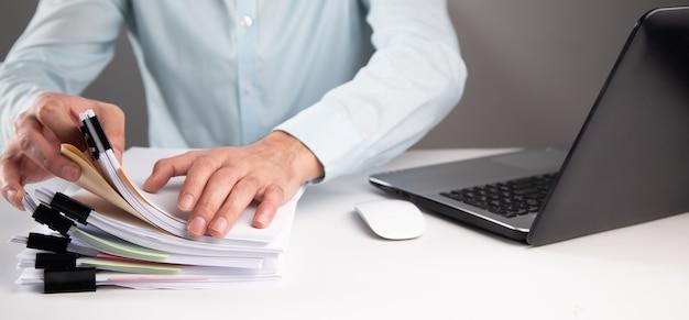Computer di lavoro dell'uomo di affari e pila di documenti