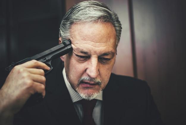Uomo di affari che lavora al computer portatile con qualcuno che indica una pistola alla sua testa