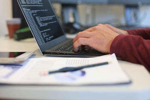 Uomo d'affari che lavora in ufficio con documenti di dati grafici sulla sua scrivania.