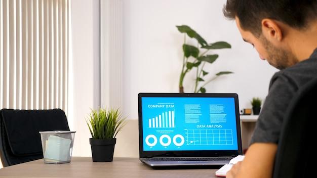 Uomo d'affari che lavora in ufficio con il computer portatile. documento sulla sua scrivania. uomo motivato