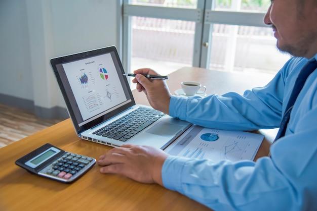 Uomo di affari che lavora all'ufficio con i documenti di dati del computer portatile, della compressa e del grafico sulla sua scrivania.