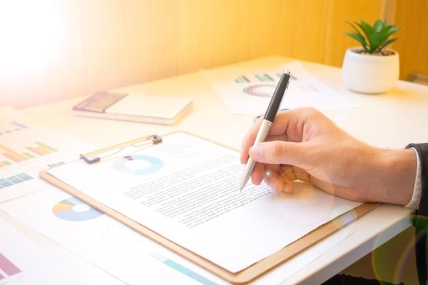 Uomo d'affari che lavora con dati finanziari - penna in mano
