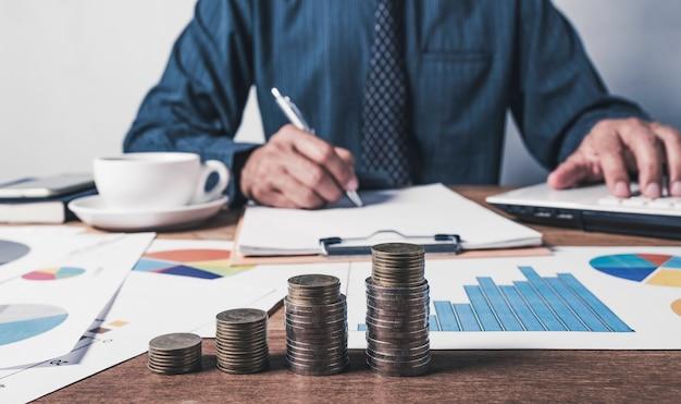 Uomo di affari che lavora e che scrive sul taccuino con la pila di monete per il concetto finanziario e contabile.