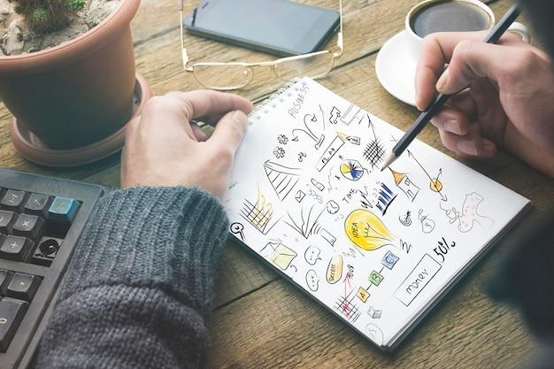 Uomo d'affari che scrive idee su carta su tavola di legno