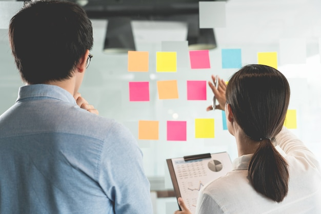 Responsabile aziendale che mostra l'idea per il suo team e incolla molti fogli di appunti sulla finestra di vetro per il successo lavorando nel concetto di ufficio creativo, pianificazione e gestione della riunione di lavoro.