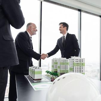 Riunione d'affari di architetti e investitori che esaminano il modello di case del quartiere residenziale