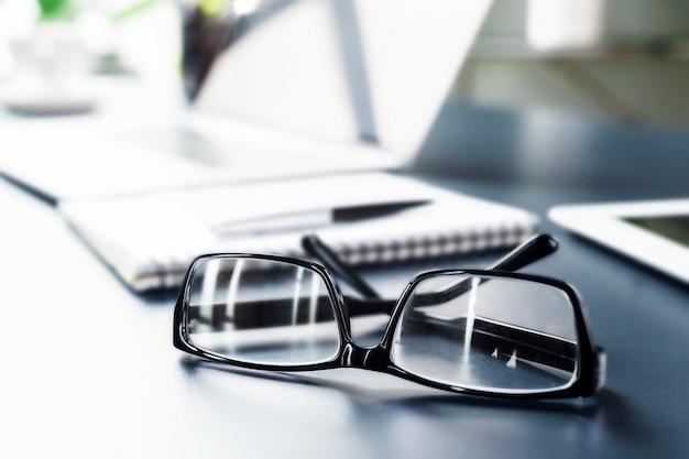 Sfondo di riunione d'affari. eleganti occhiali da vista con montatura nera sulla scrivania dell'ufficio da vicino. copia spazio