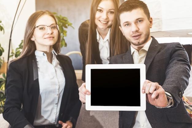 I colleghi della riunione d'affari mostrano un modello di tablet pc vuoto che mani con orgoglioso sorriso fiducioso sullo sfondo