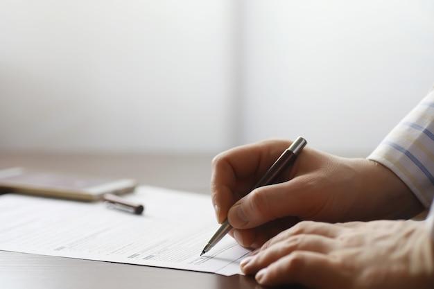Incontro di lavoro. un uomo firma un contratto. la mano maschile con la penna prende appunti in ufficio.