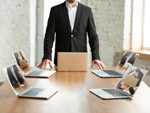 Riunione di lavoro online durante la quarantena del coronavirus. tutte le riunioni che arrivano a distanza, lavoro d'ufficio. persone che parlano utilizzando laptop durante la conferenza, indossando abiti da ufficio. dispositivo intelligente utilizzando.