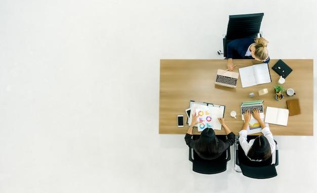 Incontro d'affari. il punto di vista superiore della squadra di buinesswoman mentre si siede insieme al tavolo dell'ufficio