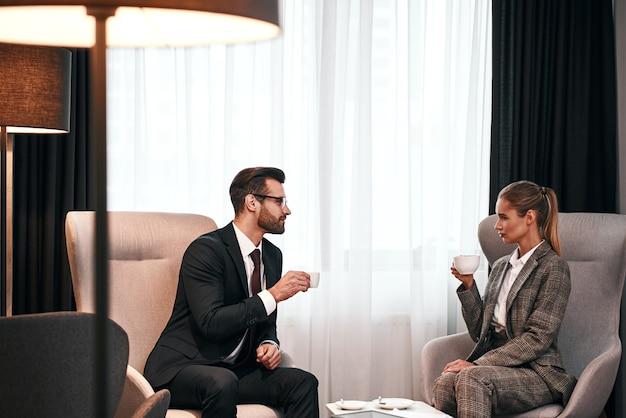 Riunione d'affari di due partner. uomo d'affari e donna che pranzano al ristorante bevendo caffè. la donna guarda l'uomo con sospetto