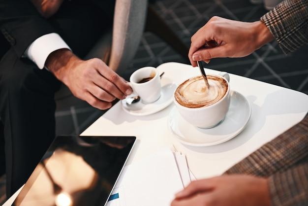 Riunione d'affari di due partner. primo piano dell'uomo e della donna che hanno pranzo di lavoro al ristorante che beve caffè. tavoletta digitale a tavola