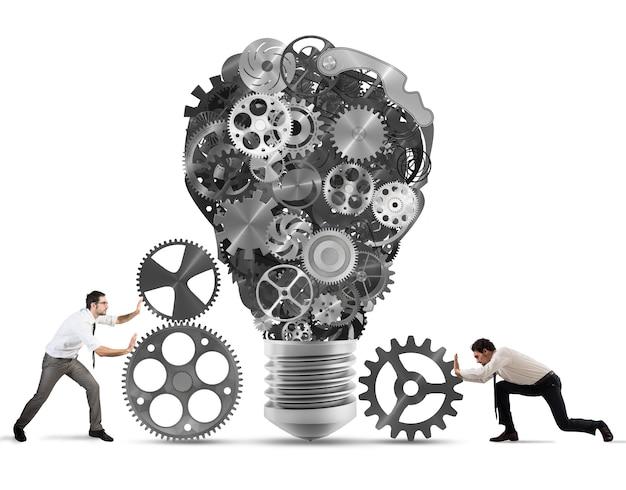 Gli uomini d'affari costruiscono una lampadina con gli ingranaggi