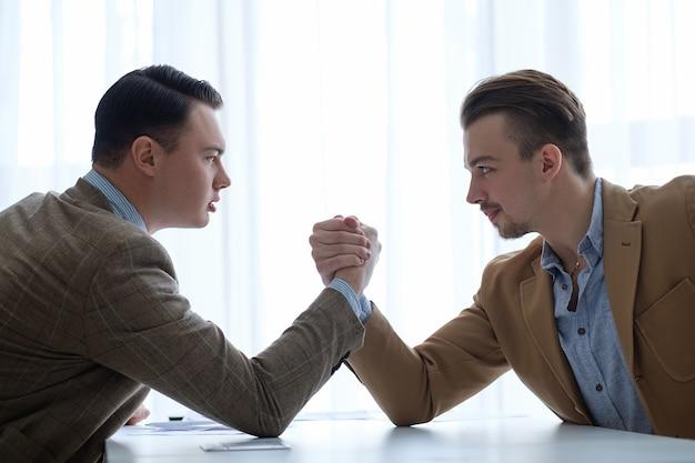 Gli uomini d'affari si confrontano e si oppongono. braccio di ferro per determinare la leadership.