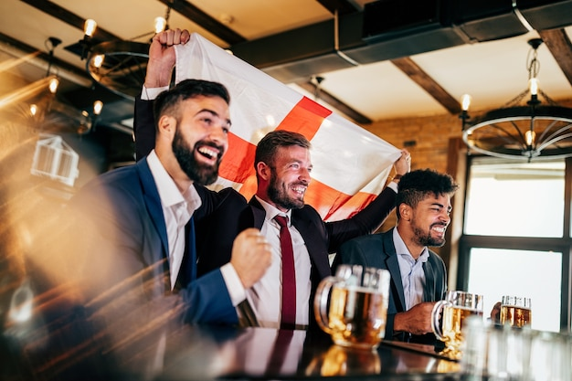 I fan degli uomini d'affari urlano e guardano il calcio in tv e bevono birra in un pub