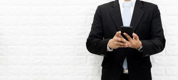 Gli uomini d'affari tengono smartphone per controllare le informazioni in ufficio