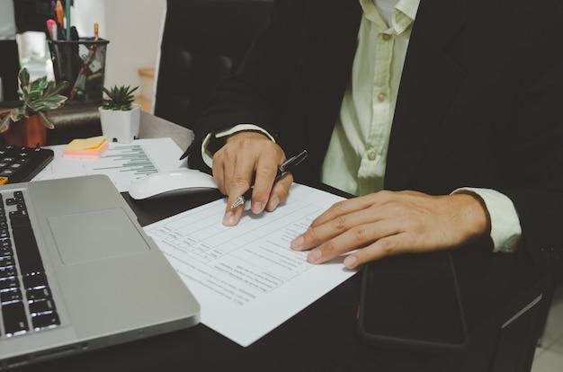 Gli uomini d'affari guardano i documenti aziendali e tengono le penne con il computer portatile e lo smart phone alla scrivania. lavoro da casa