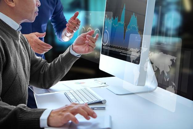 Uomini di affari che esaminano uno schermo di computer moderno che esamina un rapporto finanziario