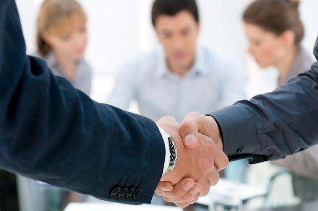Uomini d'affari si stringono la mano dopo un accordo durante una riunione