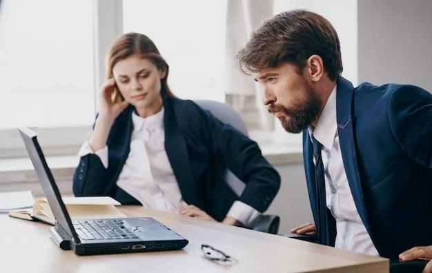 Donna e uomini d'affari si siedono a un tavolo di lavoro davanti all'ufficio di emozioni del computer portatile.