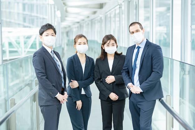 Uomini e donne d'affari che indossano una maschera e abiti