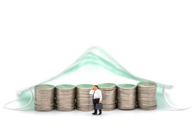 Business, denaro, covid-19 e concetto di assistenza sanitaria. la figura in miniatura dell'uomo d'affari fa una telefonata con una pila di monete d'argento sotto la maschera chirurgica su sfondo bianco.