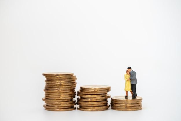 Affari, soldi, famiglia e concetto di pianificazione. la gente di figura in miniatura della donna e dell'uomo d'affari abbraccia e cammina sulla pila instabile di monete d'oro