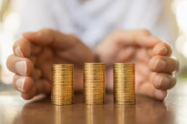 Concetto di affari, soldi, finanza, risparmio e sicurezza. la fine delle mani dell'uomo protegge tre pile di monete di oro sulla tavola di legno.