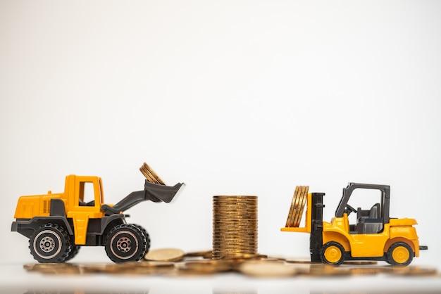 Affari, denaro e concetto finanziario. il mini modello del giocattolo dell'automobile del mini carrello elevatore e del caricatore del primo piano contiene le monete alla pila di monete d'oro su fondo bianco.