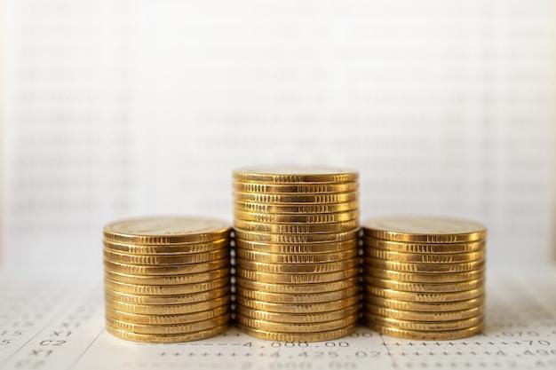 Soldi di affari e concetto finanziario. primo piano della pila di monete d'oro sul libretto di banca.