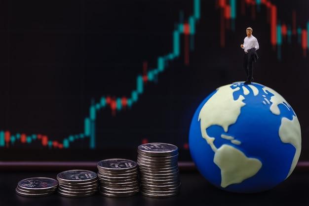 Soldi di affari, concetto finanziario e domestico. uomo d'affari figura in miniatura persone in piedi sulla mini palla del mondo con una pila di monete d'argento e grafico a candela come sfondo.