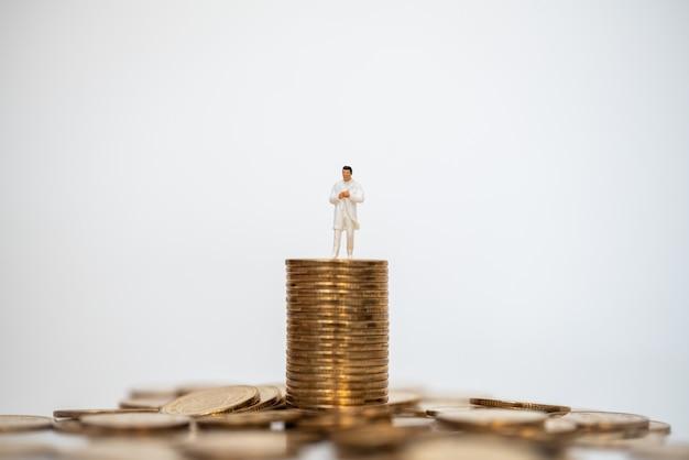 Affari, denaro concetto di assistenza sanitaria. docter figura in miniatura persone in piedi in cima alla pila e mucchio di monete d'oro sfondo bianco.