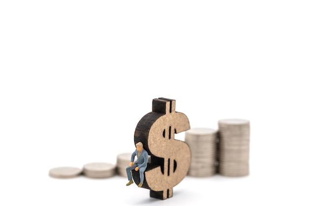 Affari, investimento di denaro e concetto di pianificazione. figura in miniatura di uomo d'affari figura seduta sul segno di legno del dollaro usa con una pila di monete d'argento su sfondo bianco.