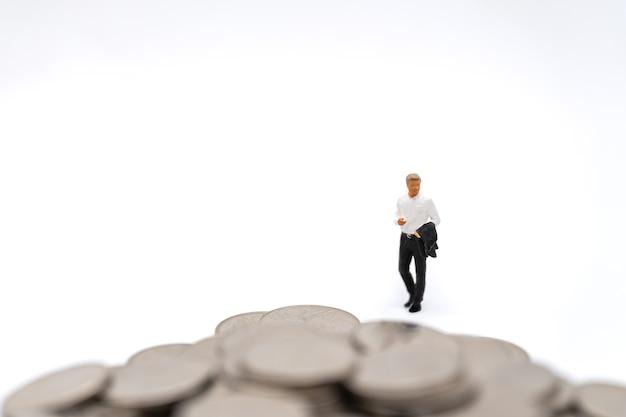 Affari, investimento di denaro e concetto di pianificazione. imprenditore figura in miniatura la gente figura a piedi al mucchio di monete d'argento su sfondo bianco.