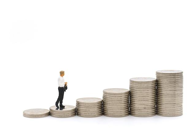 Affari, investimento di denaro e concetto di pianificazione. figura in miniatura di uomo d'affari figura che cammina su una pila di monete d'argento su sfondo bianco.