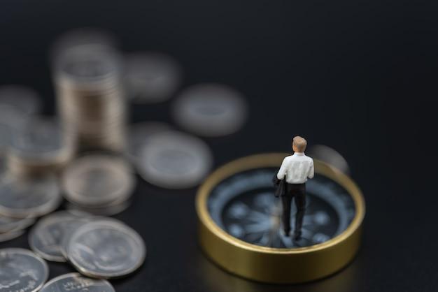 Affari, investimento di denaro e concetto di pianificazione. figura in miniatura dell'uomo d'affari figura di persone che camminano sulla bussola vintage con pila e pila di monete d'argento su sfondo nero.