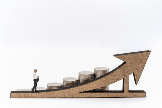 Affari, investimento di denaro e concetto di pianificazione. imprenditore figura in miniatura la gente figura camminando sul segno di freccia in legno con pila di monete d'argento su sfondo bianco.