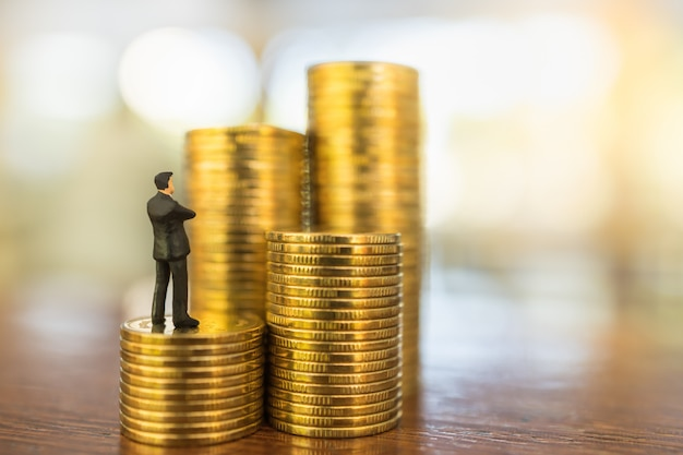 Affari, investimenti in denaro e concetto di pianificazione. chiuda su della figura miniatura della gente dell'uomo d'affari che guarda e che sta sulla pila di monete di oro sulla tavola di legno con il sapce della copia.