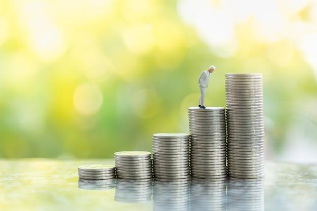 Affari, investimenti in denaro e concetto di pianificazione. chiuda su della figura miniatura della gente dell'uomo d'affari che sta sulla pila di monete d'argento con il fondo verde di anture con il sapce della copia.
